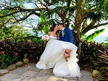bride and grrom kissing under tropical tree
