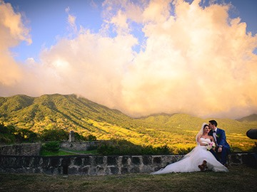 bride and groom sitting with mountain in the background