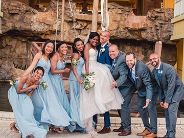 bridal party, bride and groom, and groomsmen laughing