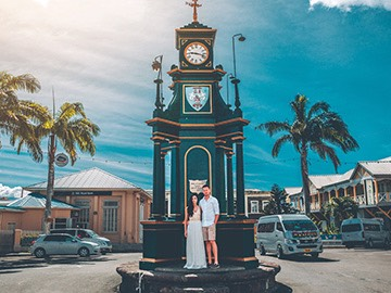 couple standing under a clocktower