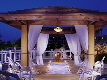 pergola with lit up wedding decorations at night