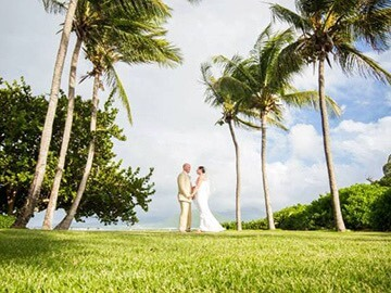 bride and groom looking at each other under palm trees