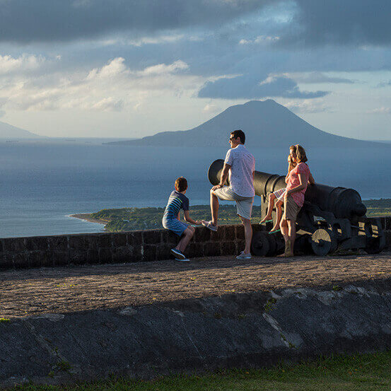family sitting on a cannon looking out over the water