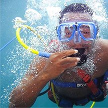 Man underwater snorkeling and surrounded by bubbles